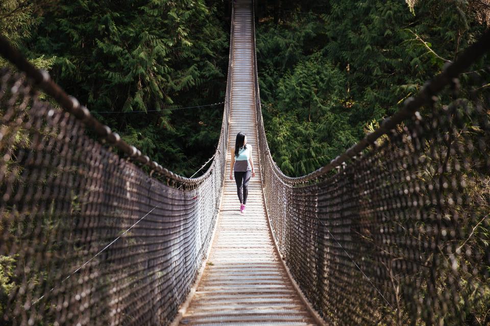 عکس رویایی دختر و عبور از پل چوبی در کوهستان و طبیعت